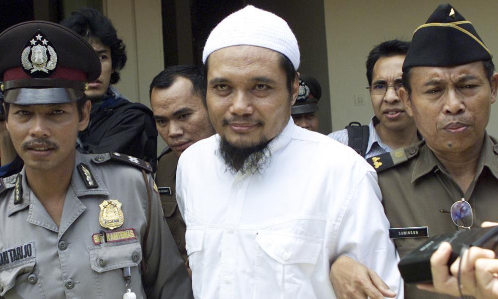 Abu Rusdan (giữa) bị áp giải sau một phiên tòa ở Jakarta, Indonesia, hồi tháng 11/2003. Ảnh: AP.