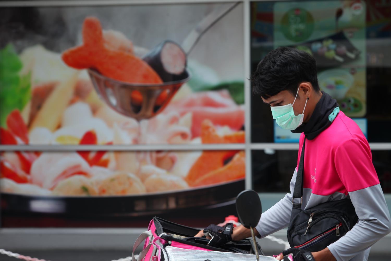 Một nhân viên giao đồ ăn mặc đồng phục hãng Foodpanda tại Thái Lan. Ảnh: Bangkok Post.