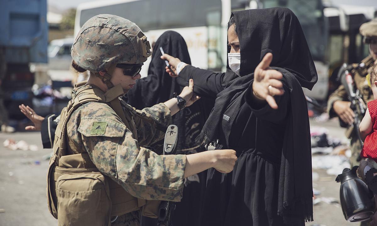 Binh sĩ Mỹ kiểm tra một người phụ nữ Afghanistan tại sân bay Hadmid Karzai ngày 28/8. Ảnh: USMC.