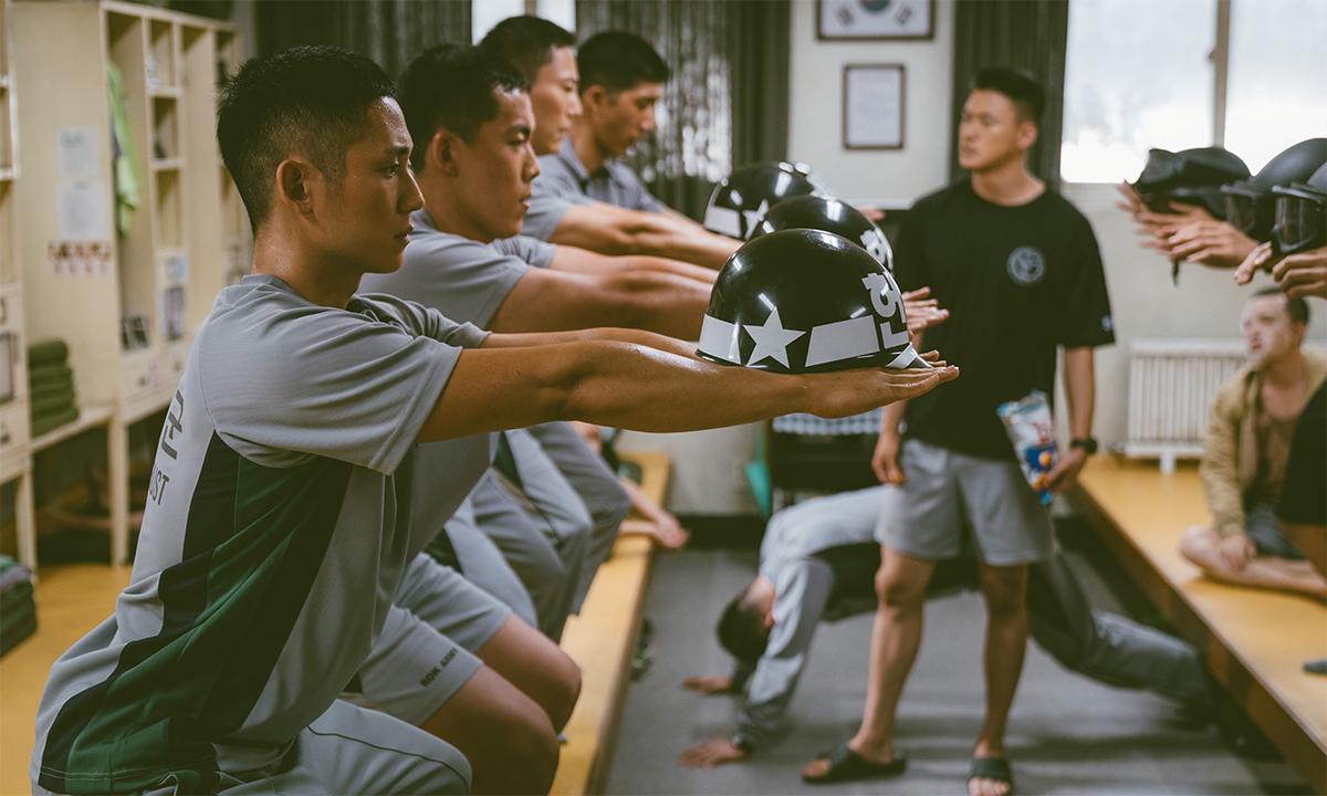 Cảnh các binh sĩ Hàn Quốc chùng gối và đỡ mũ bảo hiểm trong phim Truy bắt lính đào ngũ được chụp tháng 9/2020. Ảnh: Reuters.