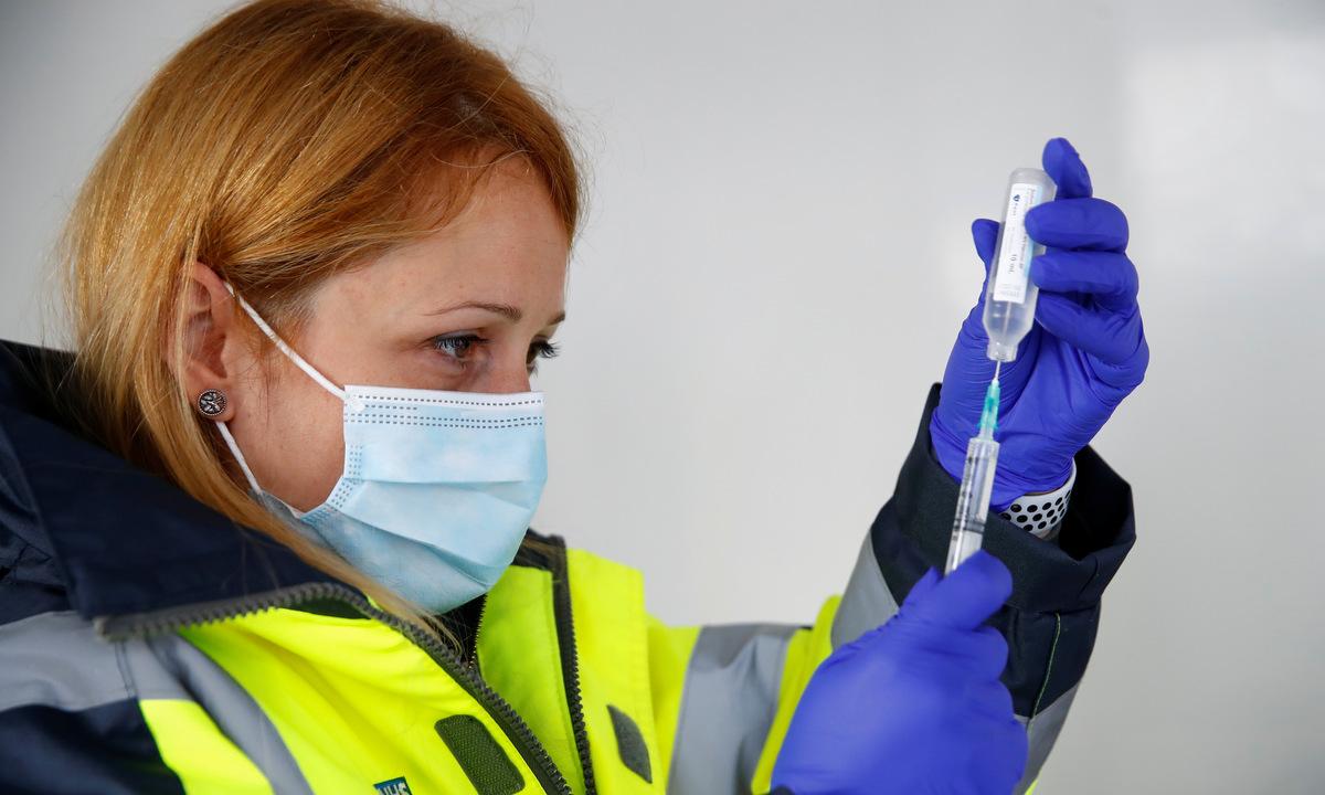 Nhân viên y tế chuẩn bị một liều vaccine Covid-19 tại Blackburn, Anh, hồi tháng 5. Ảnh: Reuters.