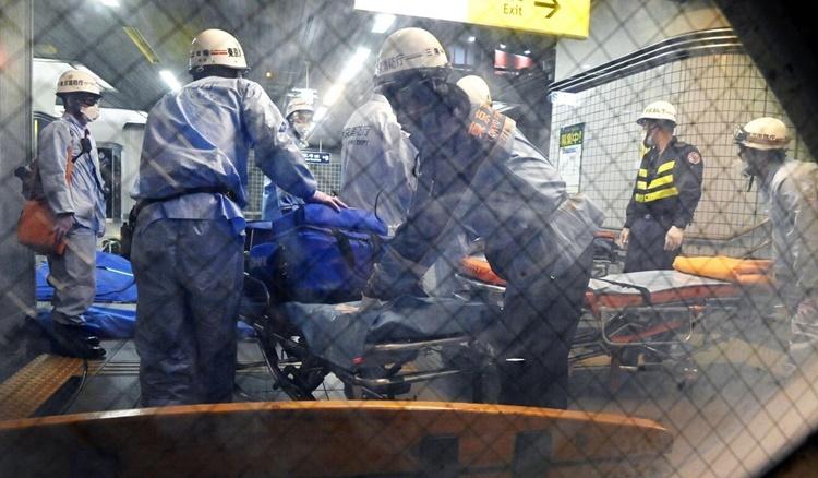 Lực lượng cứu hộ chuẩn bị cáng để hỗ trợ hành khách bị thương sau vụ đâm dao trên tàu điện ở Tokyo hồi đầu tháng trước. Ảnh: AP.