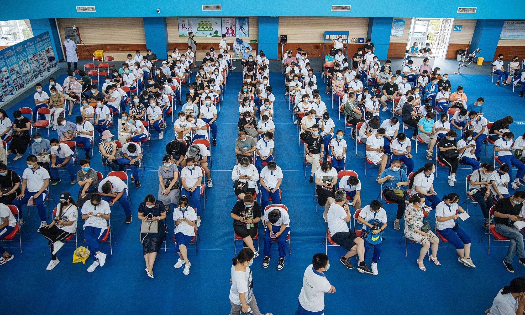 Phụ hunh và học sinh tại một trường trung học cơ sở ở Bắc Kinh chờ lượt tiêm chủng Covid-19 vào tháng 7. Ảnh: Global Times.