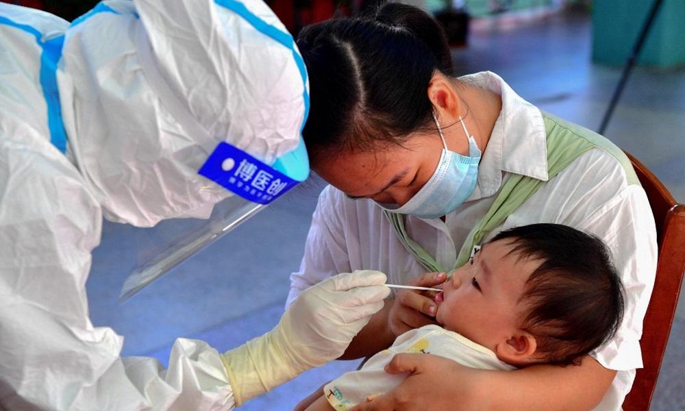 Nhân viên y tế lấy mẫu xét nghiệm Covid-19 cho một em bé ở quận Tiên Du, thành phố Phủ Điền, tỉnh Phúc Kiến hôm 13/9. Ảnh: AFP.