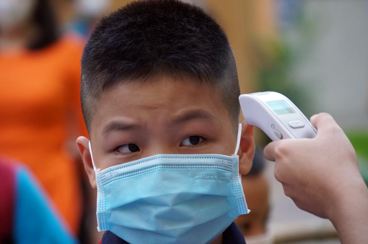 Học sinh trường Tiểu học Nguyễn Bỉnh Khiêm, quận 1 được đo thân nhiệt trước khi vào lớp học, tháng 2/2021. Ảnh: Mạnh Tùng