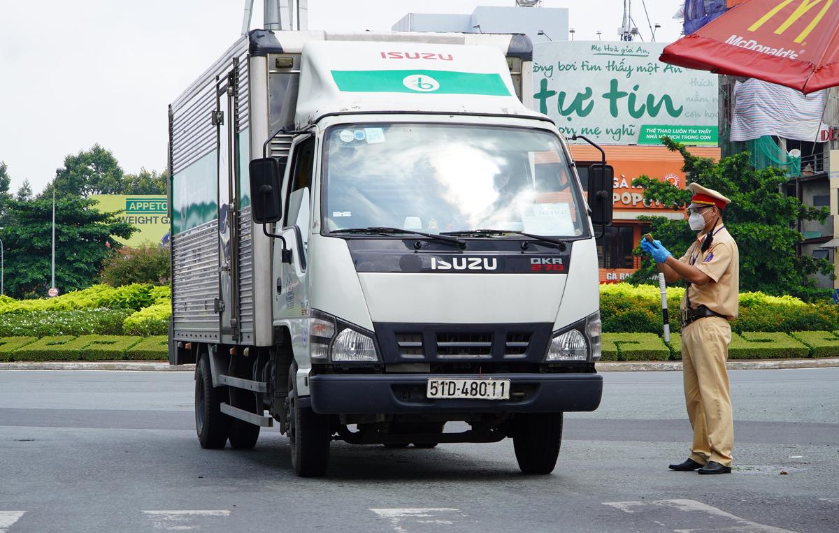Cảnh sát giao thông kiểm tra giấy tờ tài xế xe chở hàng trên đường Nguyễn Bỉnh Kiêm, quận 1 hồi cuối tháng 8. Ảnh: Gia Minh