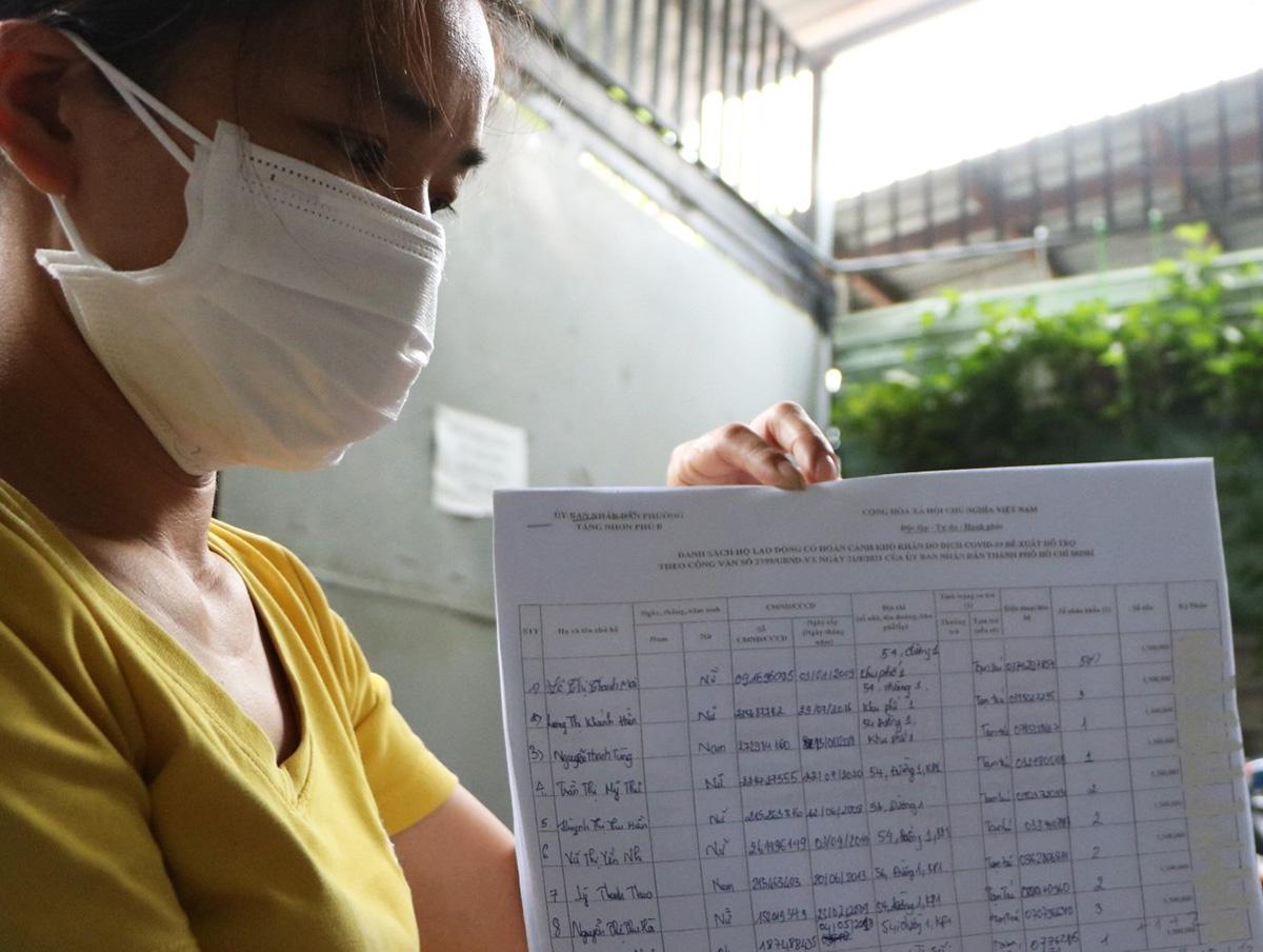 Chị Lê Thị Thanh Mai với bản kê khai người dân ký nhận tiền. Ảnh: Hà An
