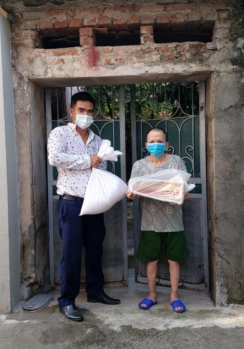 Thầy Dũng hỗ trợ một người dân khó khăn trong xã Phù Đổng suất quà trị giá 300.000 đồng, gồm 10 kg gạo, một thùng mì và tiền mặt. Ảnh: Nhân vật cung cấp