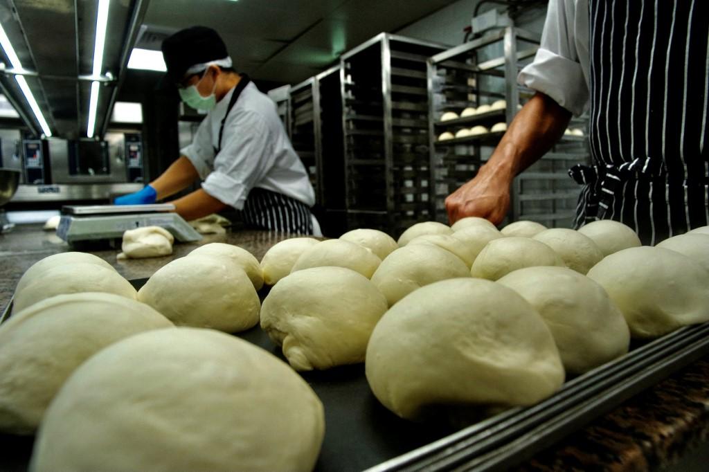 Nhân viên công ty JustKitchen Đài Loan chuẩn bị nướng bánh mỳ phục vụ đồ ăn giao hàng ở Đài Bắc hôm 18/8. Ảnh: AFP