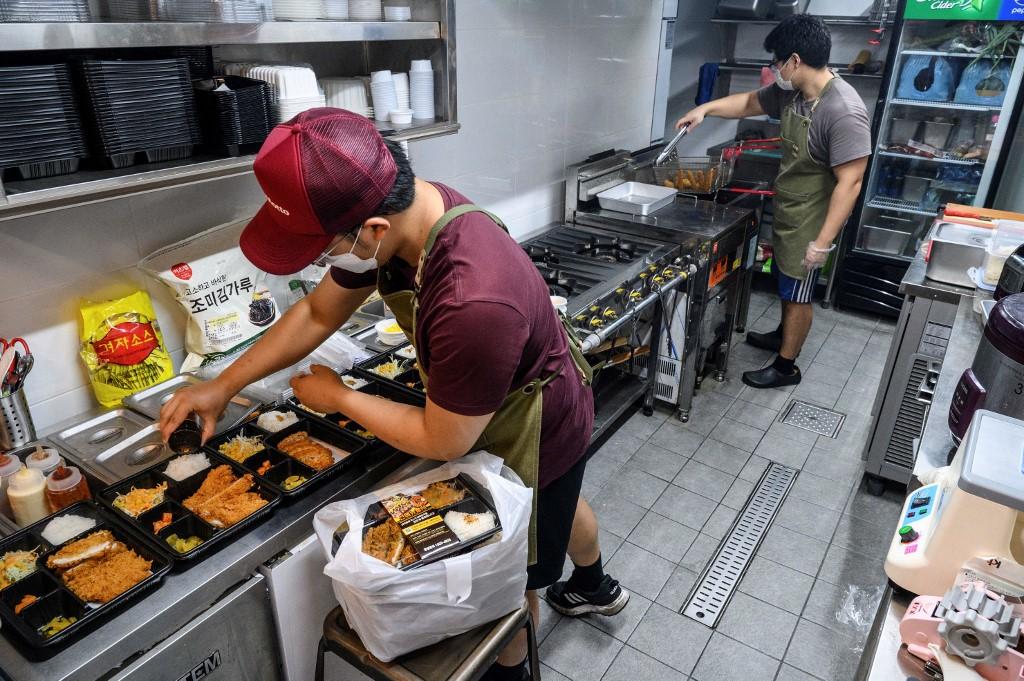 Kwon Ohshin (phải), chủ sở hữu kiêm đầu bếp của Donkatsu Kitchen, cùng đồng nghiệp chuẩn bị cơm hộp trong căn bếp ma thuê tại Seoul hôm 1/9. Ảnh: AFP