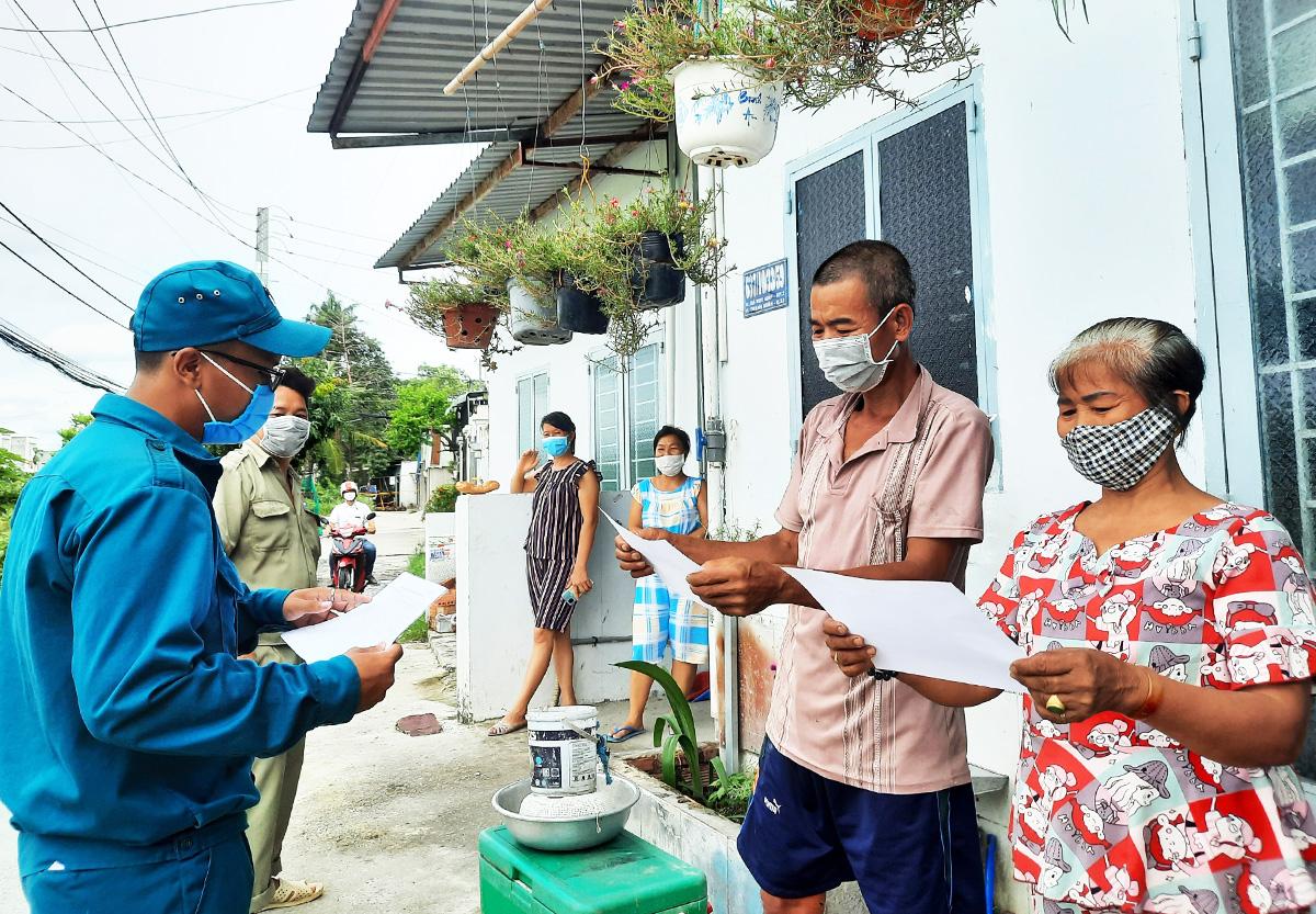 Cán bộ tổ dân phố 30, khu phố 2, phường Thạnh Xuân, quận 12, đến từng nhà lập danh sách người khó khăn để chính quyền lên kế hoạch hỗ trợ lần 3, ngày 11/9. Ảnh: Lê Tuyết