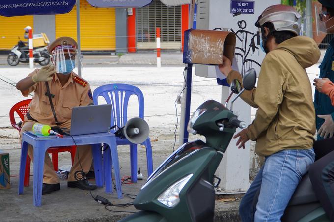 Người đi đường quét mã QR qua camera tại chốt kiểm soát đường Cách Mạng Tháng Tám, quận 3, chiều 3/9. Ảnh: Gia Minh