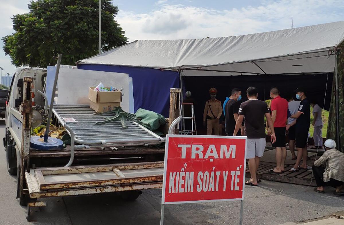 Nhà chức trách dỡ chốt ở Đại lộ Thăng Long, chiều 16/9. Ảnh: Phạm Chiểu.