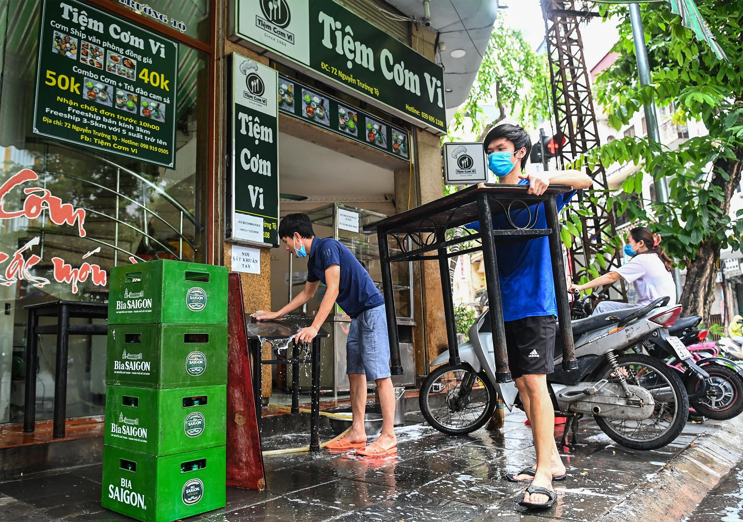 Nhân viên một quán cơm trên phố Nguyễn Trường Tộ (quận Ba Đình) tất bật lau dọn bàn ghế, chuẩn bị mở bán vào ngày 17/9. Ảnh: Giang Huy