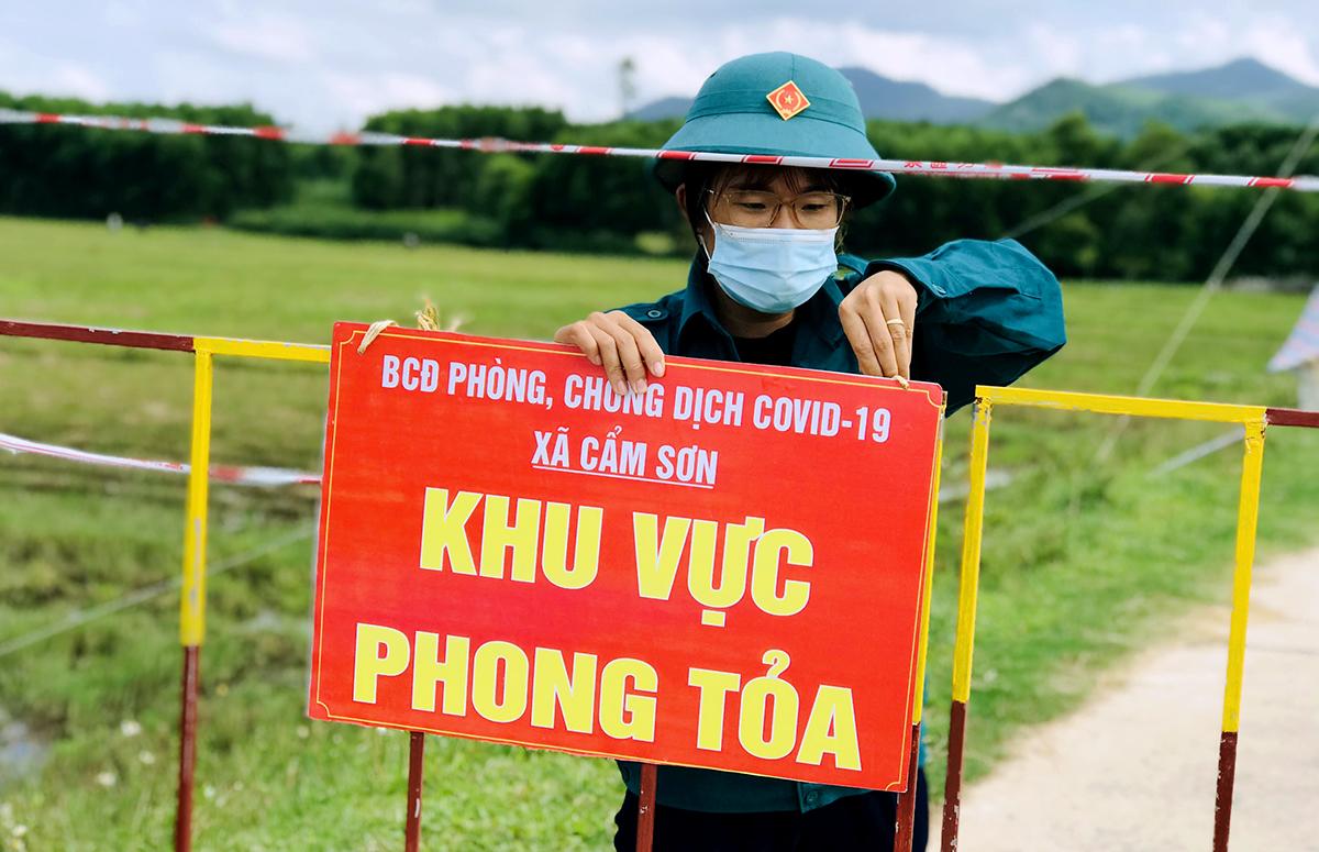 Cán bộ địa phương tháo biển thông báo khu vực phong tỏa tại một chốt kiểm soát ở thôn Vinh Sơn, xã Cẩm Sơn, chiều 16/9. Ảnh: Hùng Lê