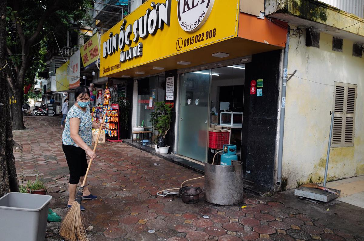 Nhân viên tại quán bún ốc trên phố Tô Hiệu, Cầu Giấy lau dọn quán sau gần 2 tháng đóng cửa, sáng 16/9. Ảnh: Ngọc Thành.