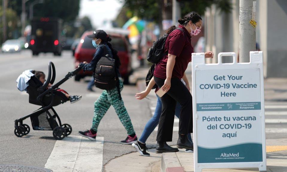 Người dân đeo khẩu trang đi qua biển chỉ dẫn điểm tiêm chủng Covid-19 tại thành phố Los Angeles, bang California, Mỹ, hôm 17/8. Ảnh: Reuters.