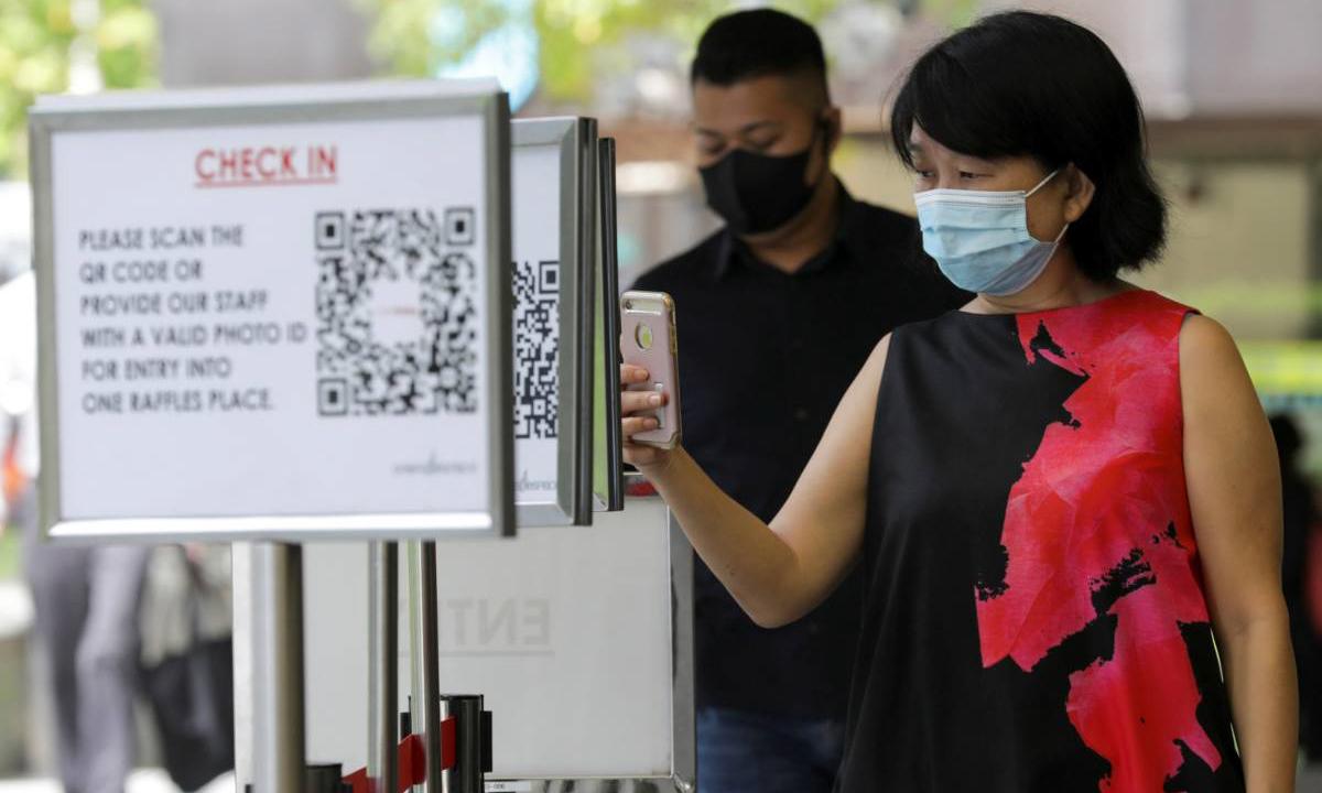 Một người phụ nữ quét mã QR trước khi vào trung tâm mua sắm ở Singapore hồi tháng 5. Ảnh: Reuters.