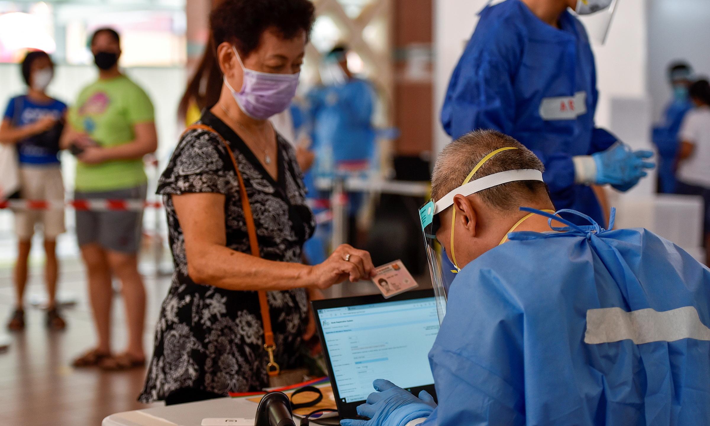 Nhân viên y tế Singapore kiểm tra thông tin của một người tới xét nghiệm nCoV ngày 16/6.