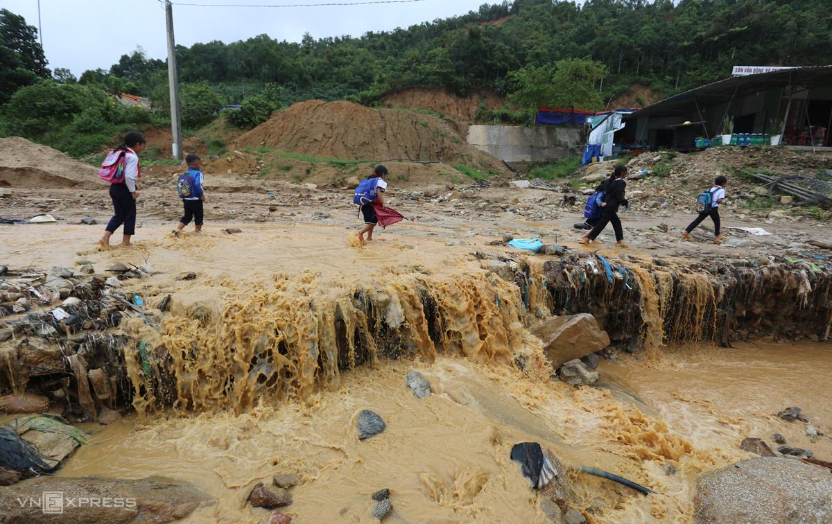 Học sinh lội nước trên đường ĐH1 đoạn qua trung tâm xã Phước Thành nước chảy băng qua đến trường. Ảnh: Đắc Thành.