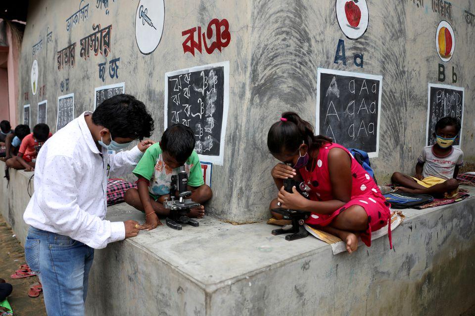 Thầy Nayak quan sát các em nhỏ thực hành với kính hiển vi. Ảnh: Reuters