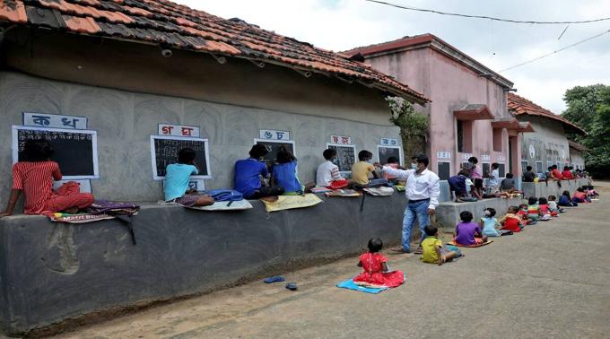 Thầy Deep Narayan Nayak (áo trắng) dạy các em không có thiết bị học trực tuyến tại một lớp học ngoài trời, bên ngoài những ngôi nhà có tường sơn thành bảng đen ở làng Joba Attpara, quận Paschim Bardhaman, bang West Bengal, hôm 13/9. Ảnh: Reuters
