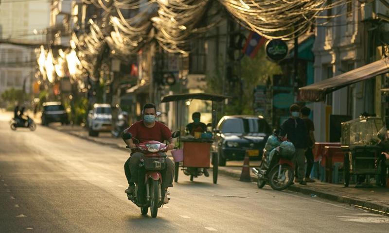 Người lái xe máy đeo khẩu trang di chuyển trên đường phố Vientiane hôm 19/6. Ảnh: Xinhua