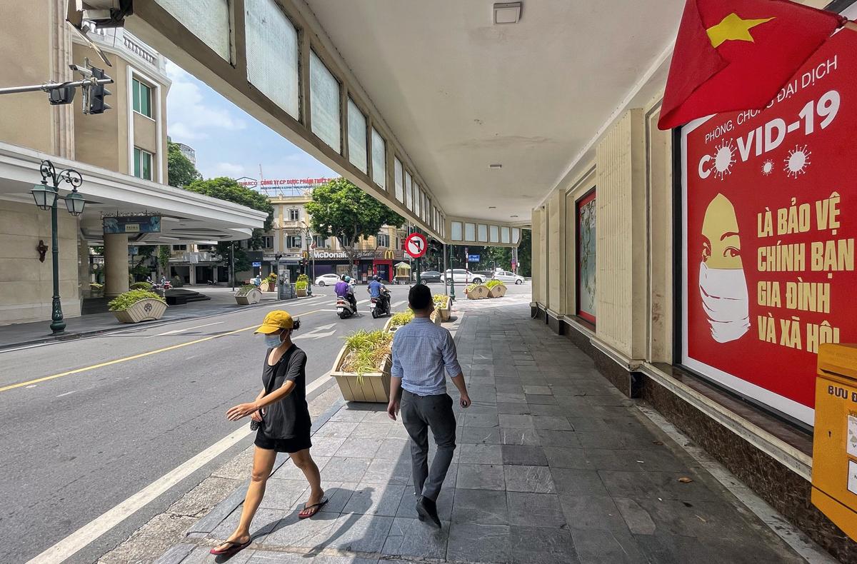 Người dân đi qua tấm pano tuyên truyền phòng dịch Covid - 19 trên phố Tràng Tiền (Hoàn Kiếm), sáng 20/9. Ảnh: Giang Huy.