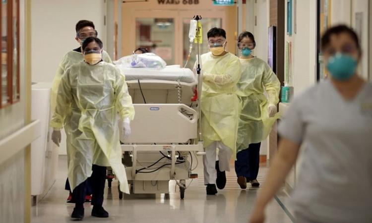 Nhân viên y tế tại Bệnh viện Đa khoa Singapore di chuyển một bệnh nhân Covid-19 tới khu điều trị cách ly hồi năm ngoái. Ảnh: Straits Times.