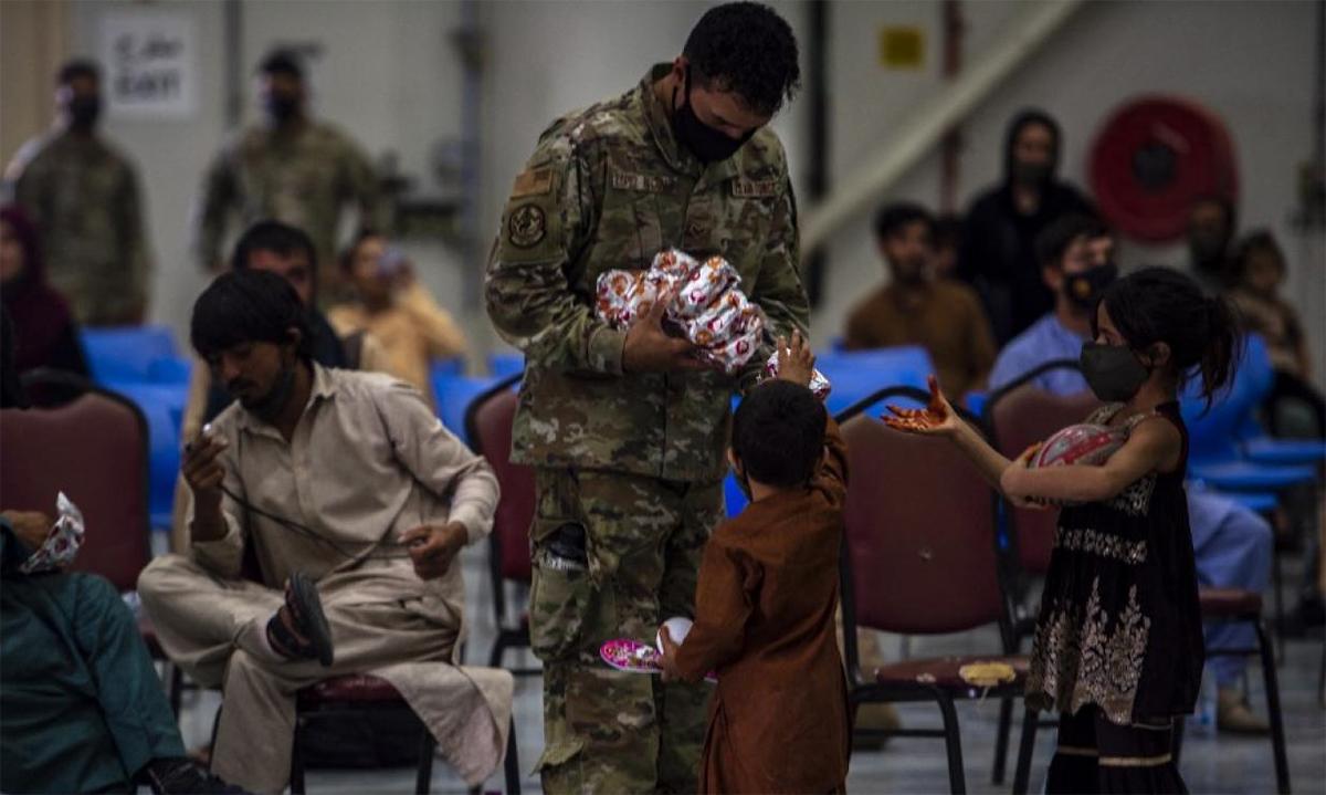 Binh sĩ Mỹ phát lương thực cho dân tị nạn Afghanistan tại căn cứ al-Adeid ở Qatar ngày 16/8. Ảnh: USCENTCOM.