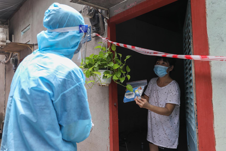 Nhân viên y tế phát túi thuốc F0 cho bệnh nhân ở quận 8. Ảnh: Quỳnh Trần.
