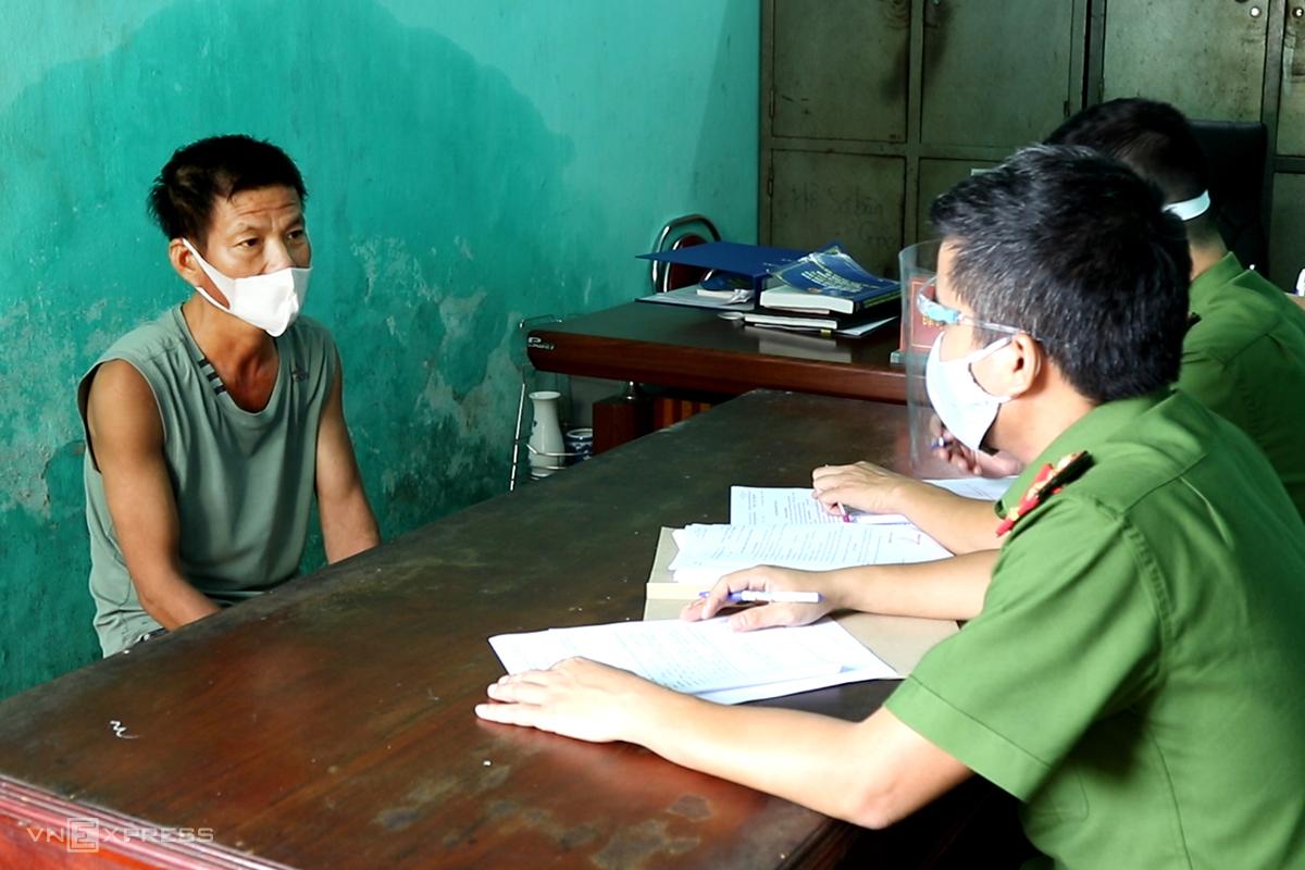 Ông Sơn (bên trái) làm việc với công an. Ảnh: Quang Văn