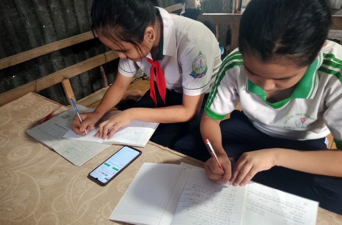 Nguyễn Thị Có, lớp 8 (phải) và em ruột Nguyễn Thị Thuỳ Linh, lớp 6, cùng học online bằng một điện thoại của cha mẹ. Ảnh: Đức Duy