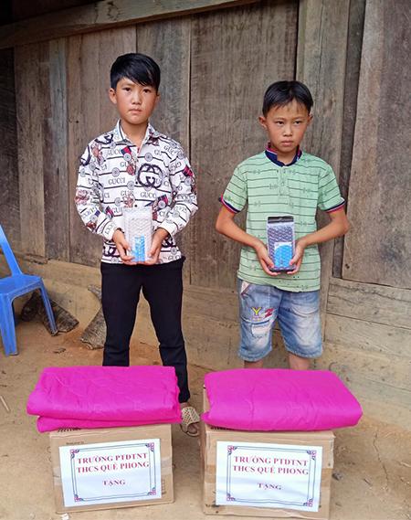 Dần và Thành nhận quà từ trường Dân tộc nội trú THCS Quế Phong. Ảnh: CTV