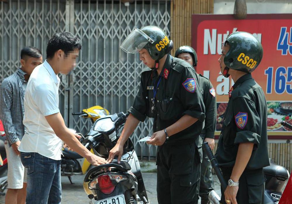Xử phạt người đi xe máy không đội mũ bao hiểm ở Hà Nôi. Ảnh: Phương Sơn.