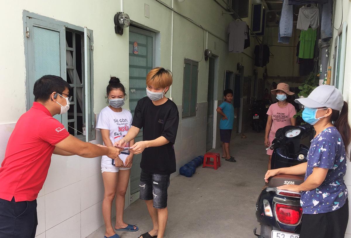 Công nhân ở xóm trọ phường Đông Hưng Thuân, quận 12 nhận hỗ trợ từ nhà hảo tâm. Ảnh: Lê Tuyết