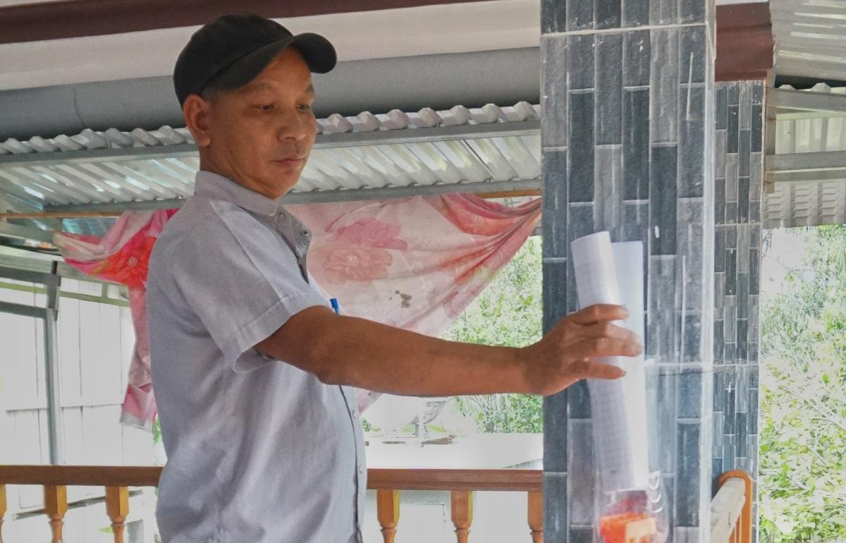 Thầy Đinh KaMach tới nhà học sinh bỏ bài học vào ống nhựa. Ảnh: Phạm Linh