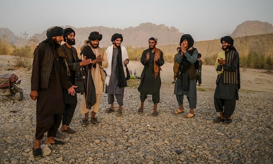 Nhóm thanh niên Taliban nhảy múa dưới chân một cây cầu gần thành phố Kandahar, Afghanistan ngày 23/9. Ảnh: AFP.