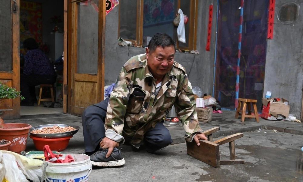 Minh Kim Thành dùng ghế đẩu di chuyển trong sân nhà ở thôn Thạch Khôi Diêu, thành phố Nhật Chiêu, tỉnh Quảng Đông, hôm 10/9. Ảnh:QQ