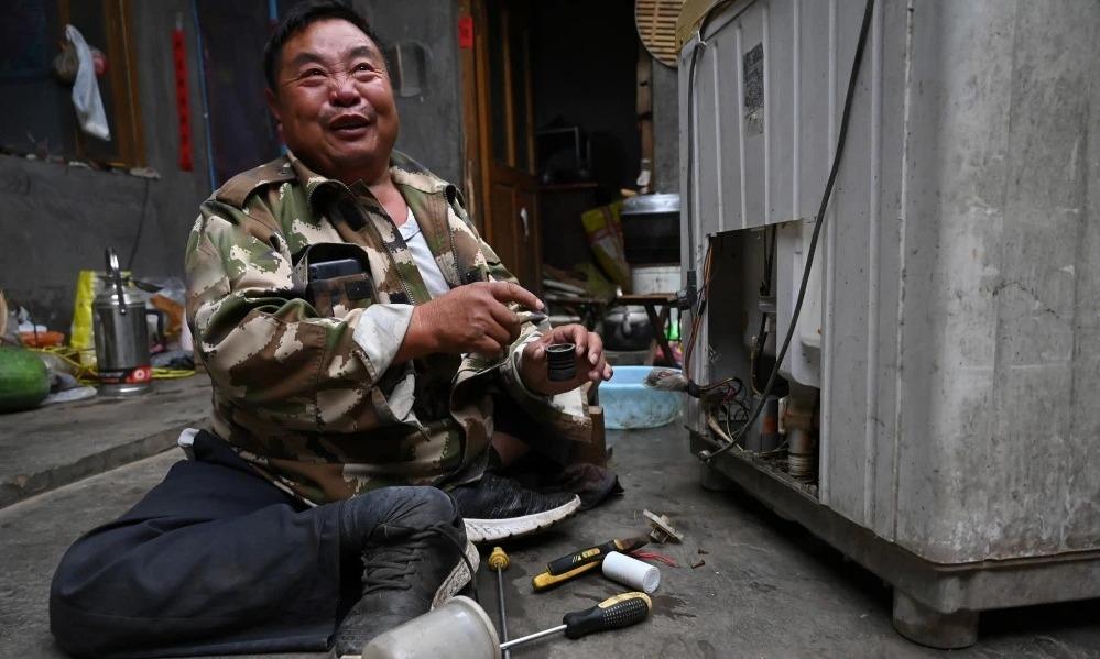 Minh Kim Thành vừa sửa chữa đồ điện, vừa tâm sự câu chuyện đời mình. Ảnh: QQ