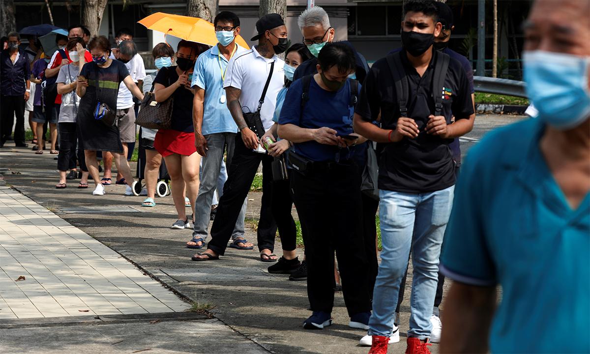 Dân Singapore xếp hàng chờ bên ngoài một trung tâm xét nghiệm nhanh nCoV ngày 21/9. Ảnh: Reuters.