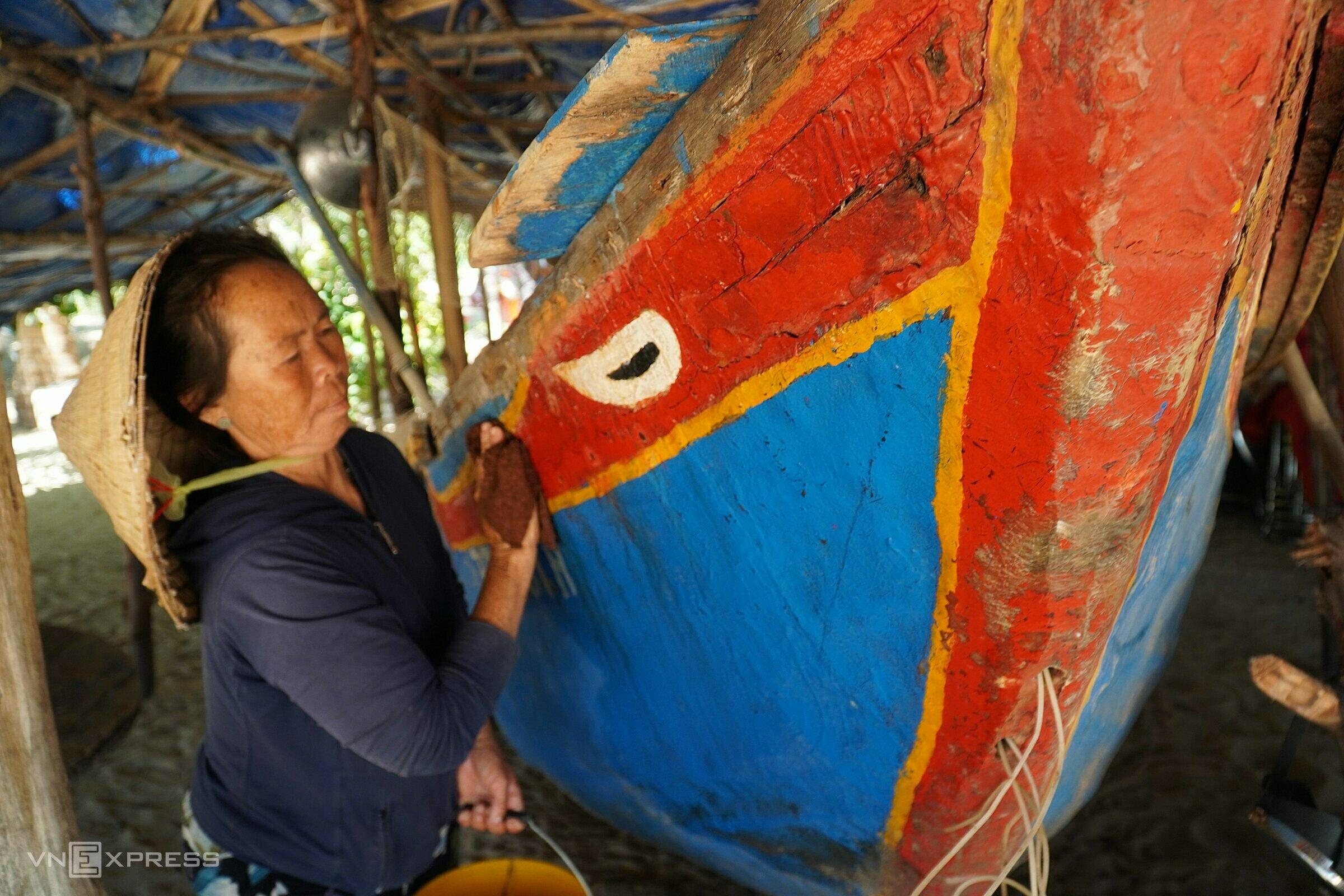 Bà Trần Thị Đợi, vợ ông Phụng lau chùi lại chiếc thuyền kỷ vật. Ảnh: Việt Quốc