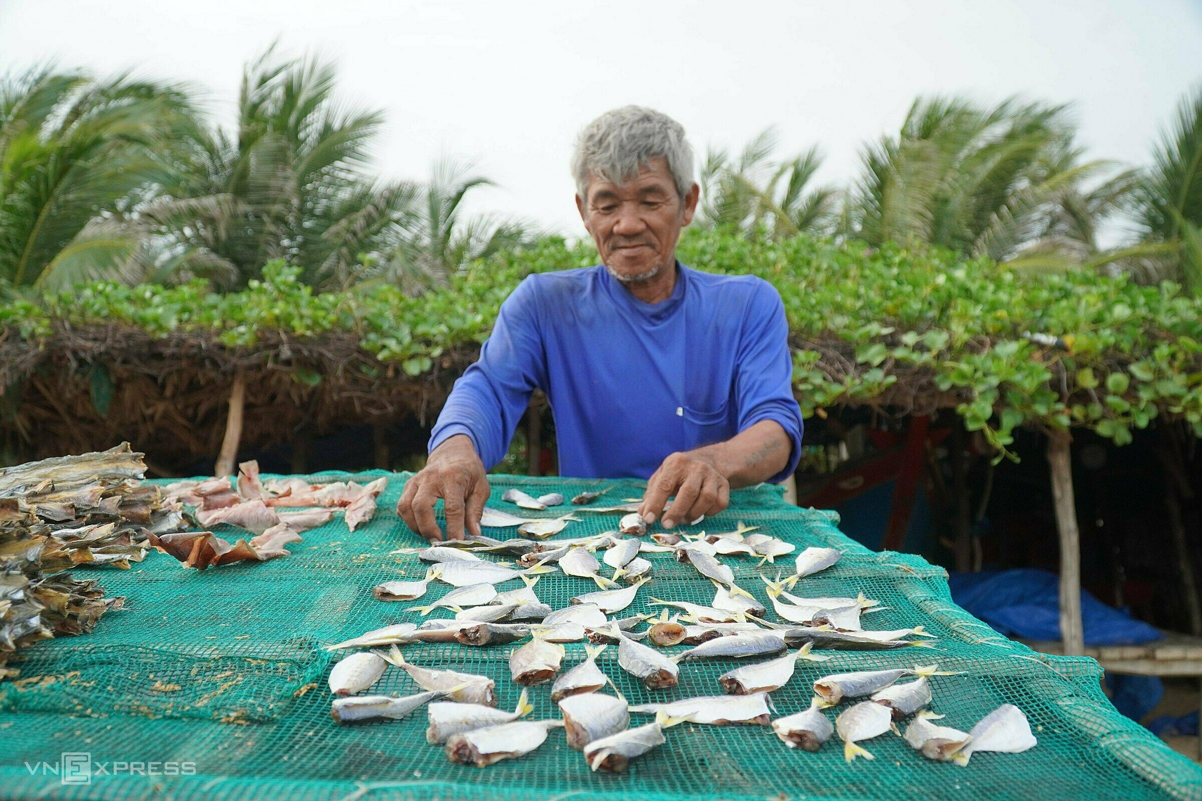 Ông Phụng trở cá khô do vợ xẻ phơi trước biển Hòn Nghề, xã Hòa Thắng. Ảnh: Việt Quốc