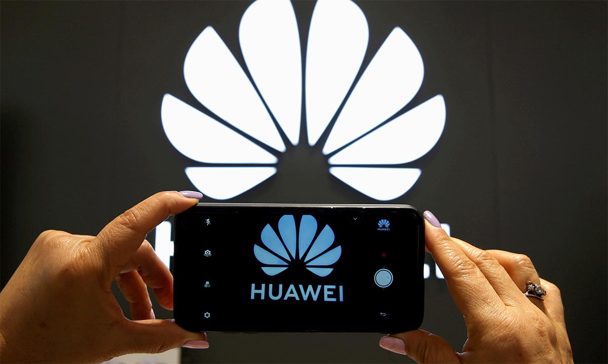 Một người phụ nữ cầm điện thoại chụp ảnh biểu tượng Huawei trong của hàng của hãng ở thành phố Vina del Mar, Chile tháng 7/2019. Ảnh: Reuters.