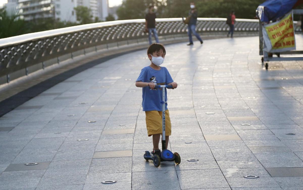 Một bé trai chơi xe Scooter trên cầu Ánh Sao, quận 7. Ảnh: Đình Văn