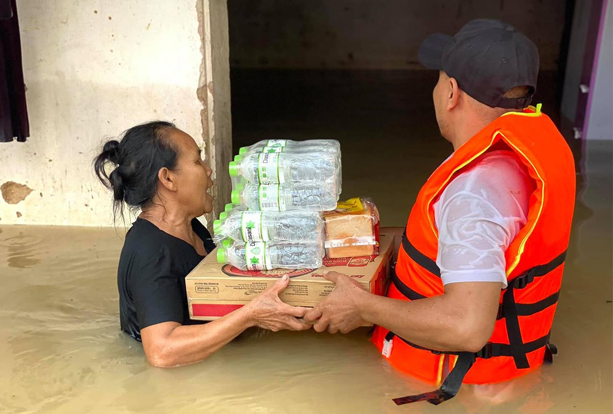 Hộ dân nhận nước uống, mì tôm từ lực lượng cứu hộ. Ảnh: Dũng Nguyễn