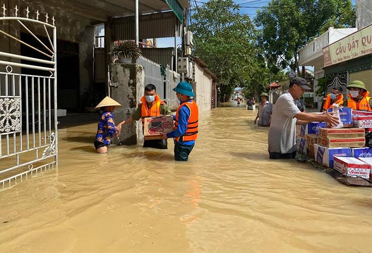Lực lượng chức năng trao lương thực cho người dân ở xã Quỳnh Lâm. Ảnh: Quỳnh Lưu
