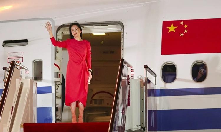 Mạn Vãn Chu vẫy tay chào khi bước ra cửa phi cơ tại sân bay Bảo An Thâm Quyến, Trung Quốc, tối 25/9. Ảnh: Xinhua.