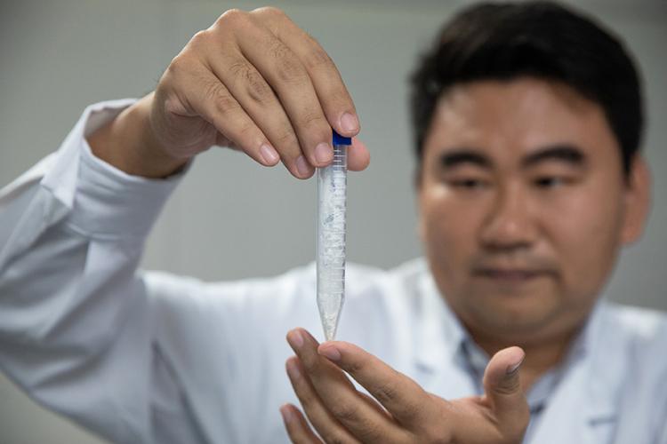 Nhà nghiên cứu Cai Tao cầm mẫu tinh bột được tổng hợp trong phòng thí nghiệm. Ảnh: Xinhua