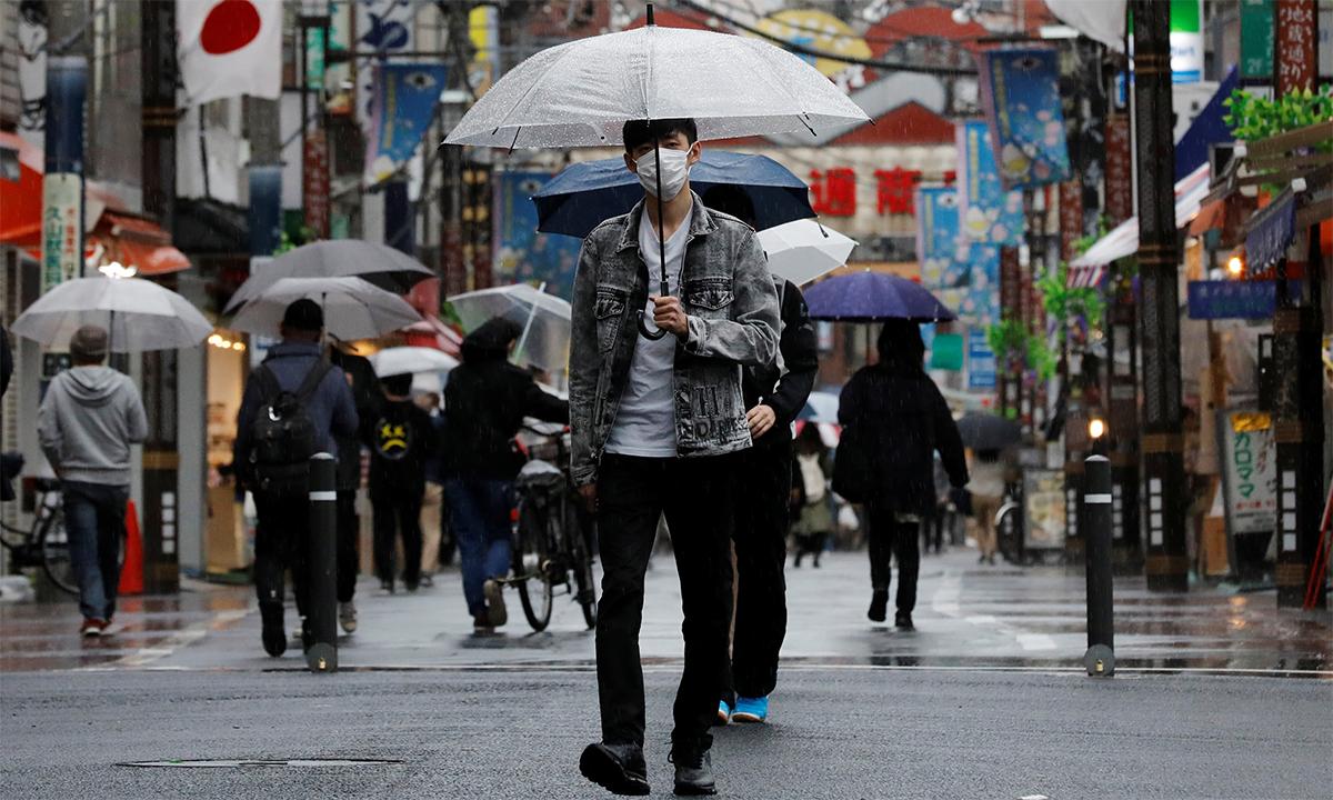 Một thanh niên Nhật Bản đeo khẩu trang đi trên đường phố thủ đô Tokyo ngày 5/5. Ảnh: Reuters